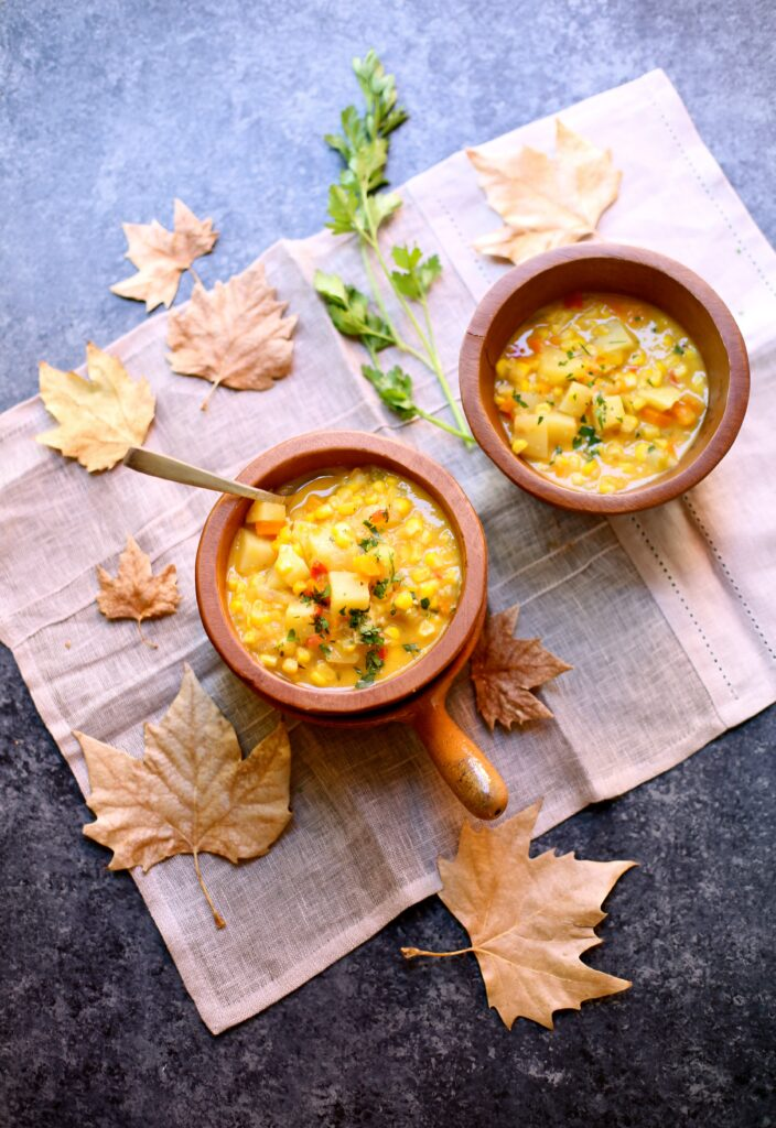 Two bowls of Fresh Corn Chowder in wooden bowls with autumn leaves on a tablecloth and a dark table