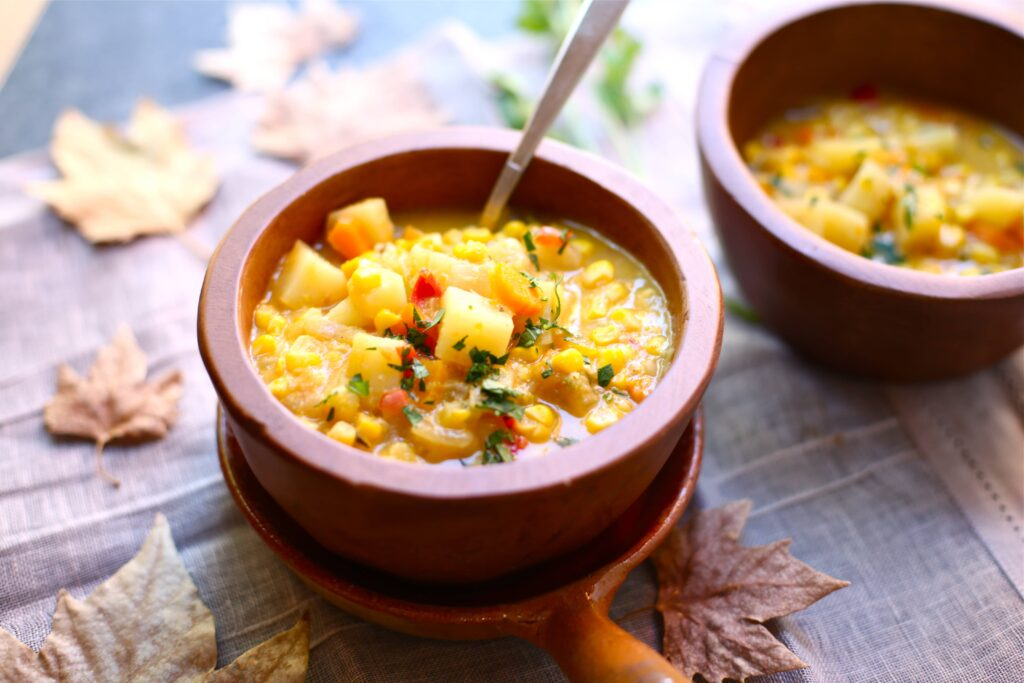 Two bowls of Fresh Corn Chowder in wooden bowls on a table with fall leaves