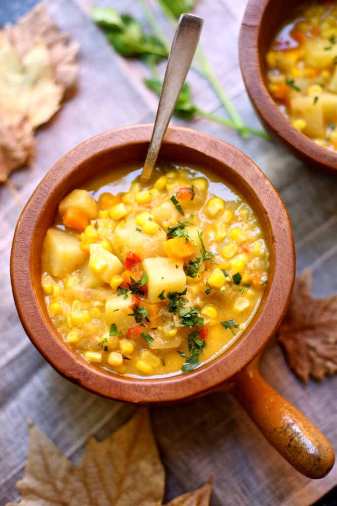 Fresh Corn Chowder in a wooden bowl with a spoon coming out with leaves around the table