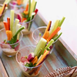 Veggies in plastic cups on a wooden tray