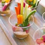 veggies in a plastic cup with hummus