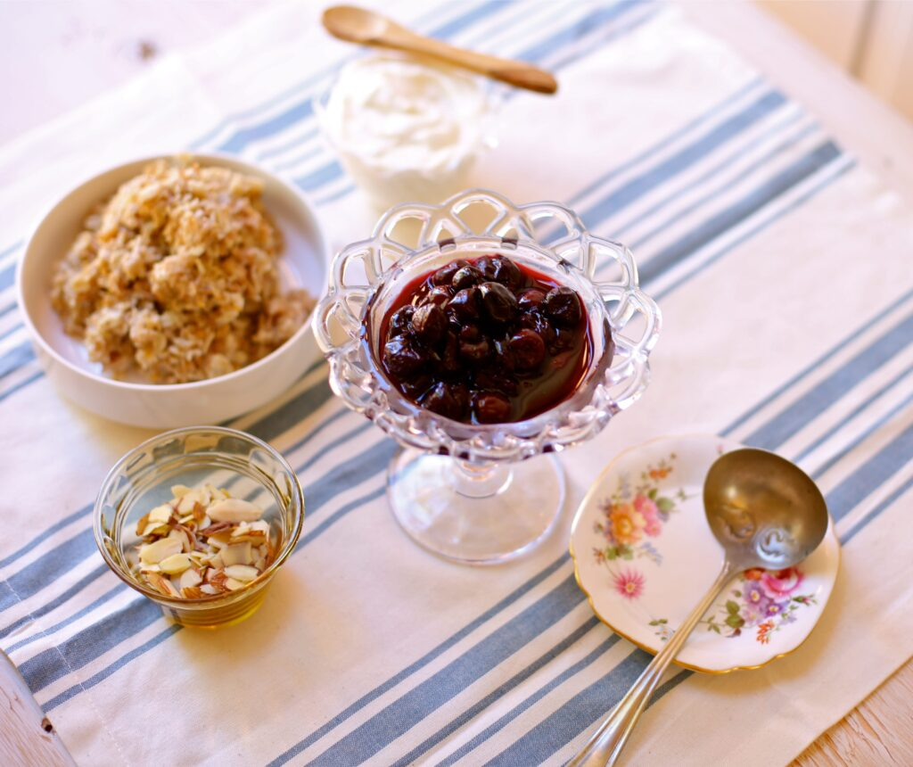 Cherry compote, plain oatmeal, sliced almonds and yogurt with a wooden spoon