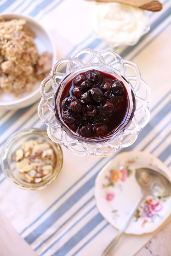 Cherry compote surrounded by sliced almonds and plan oatmeal and a silver spoon