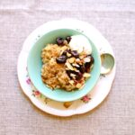 Oatmeal with Cherry Almond Compote in a dish on a small platter and bowl