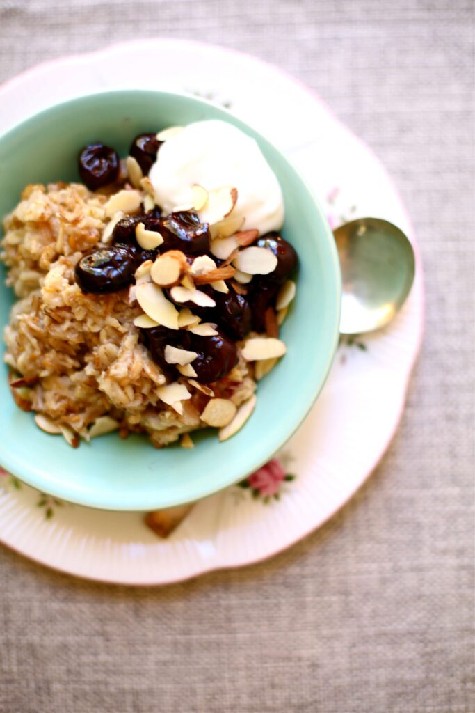 Cherry Almond Oatmeal in a blue bowl with cherries and yogurt and almonds with a spoon