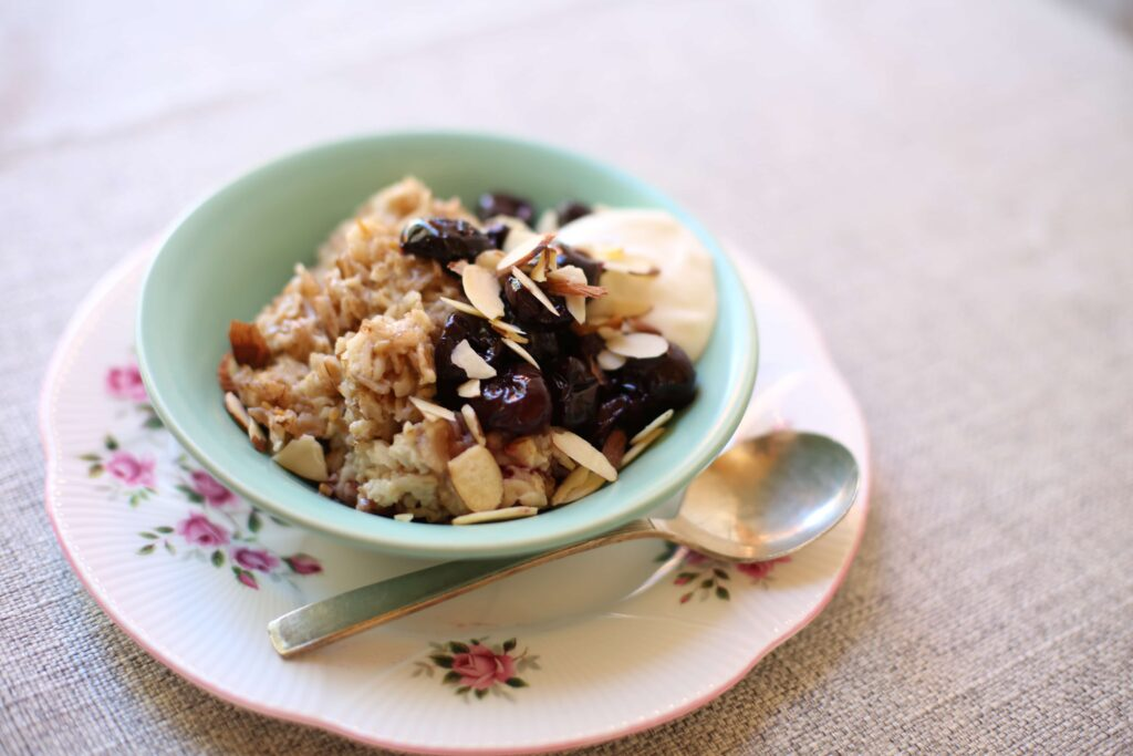 Cherry Almond Oatmeal in a blue bowl on a white plate with a silver spoon