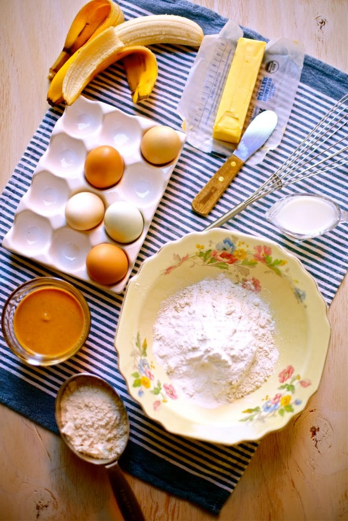 Ingredients for Peanut Butter Banana Pancakes, eggs, flour, peanut butter, butter, banana and a whisk on a blue and white striped towel