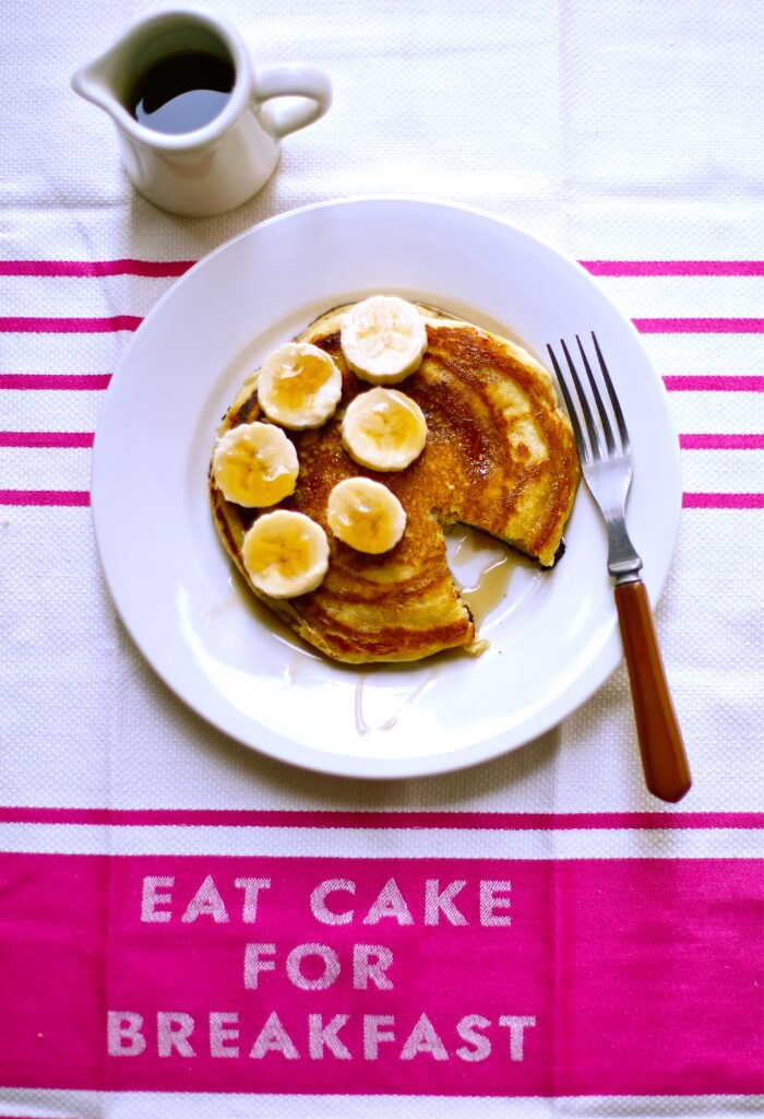 Peanut Butter Banana Pancakes on a towel that says eat cake for breakfast, with a white plate and side of maple syrup