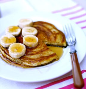Pancakes and bananas on a plate with a fork