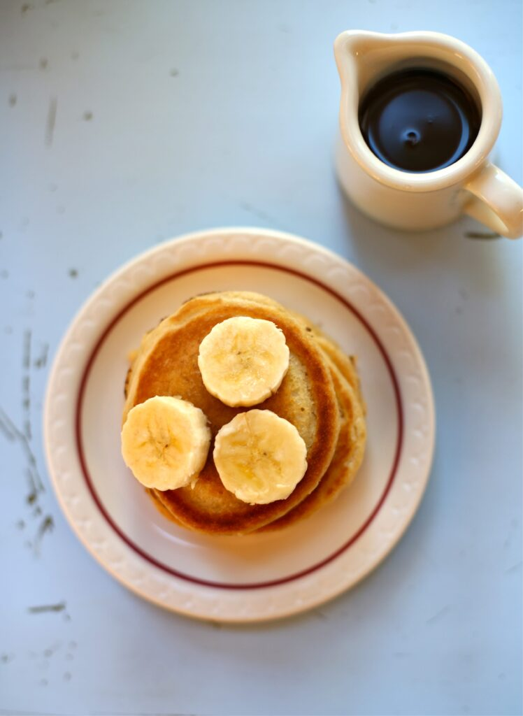 Peanut Butter Banana Pancakes on a blue board with a white pourer with maple syrup