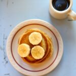 Pancakes with bananas and syrup on a blue table