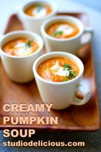 Cups of Creamy Pumpkin Soup in white bowls on a wooden board with text in the photo