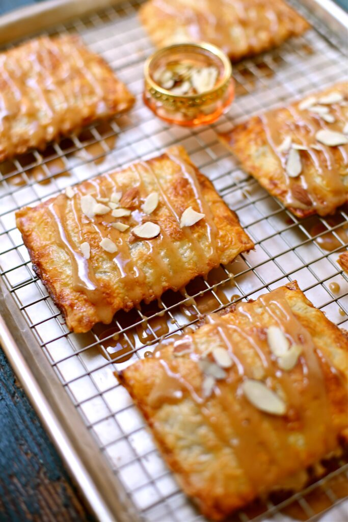 Apple Butter Hand Pies by Studio Delicious on a baking rack with sliced almond