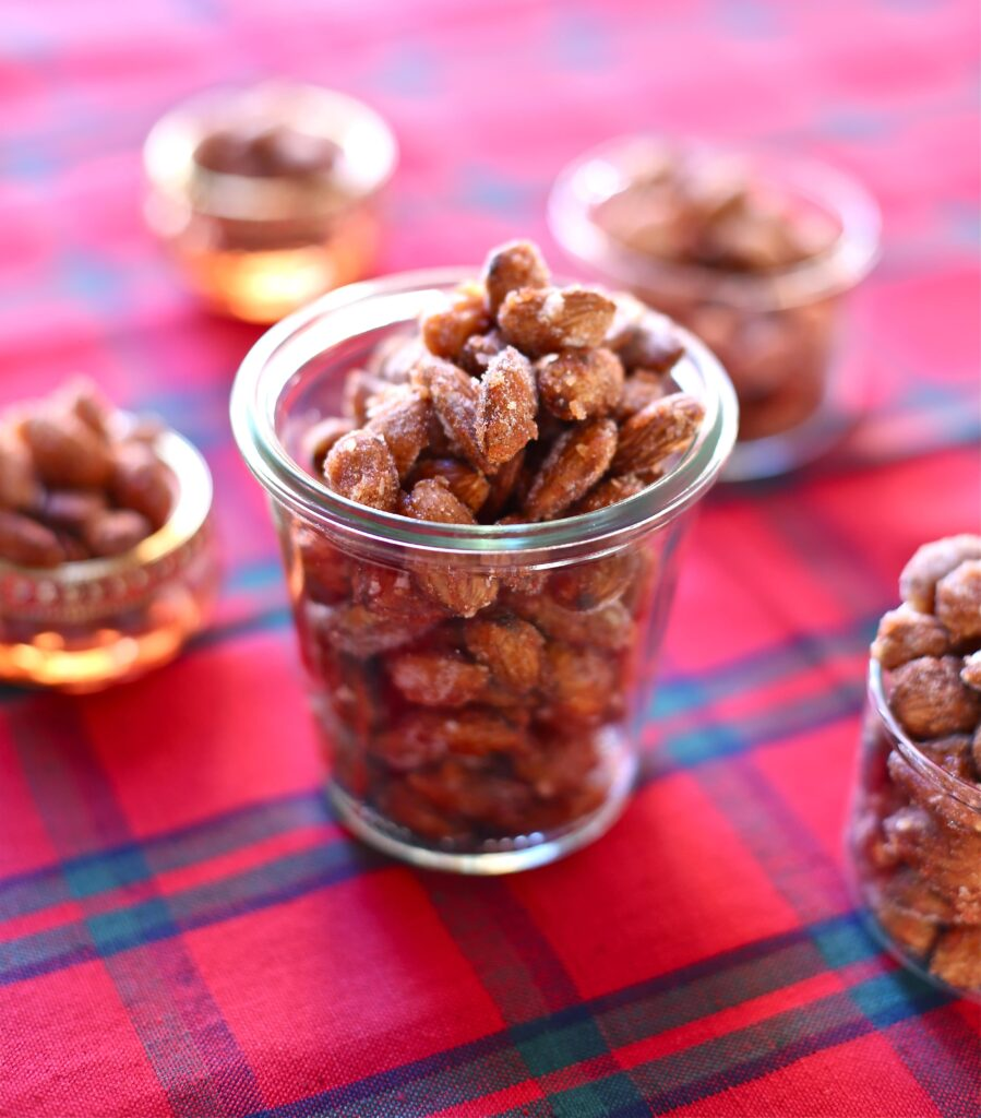 Sweet and Spicy Almonds on a plaid tablecloth and small jars next to iot
