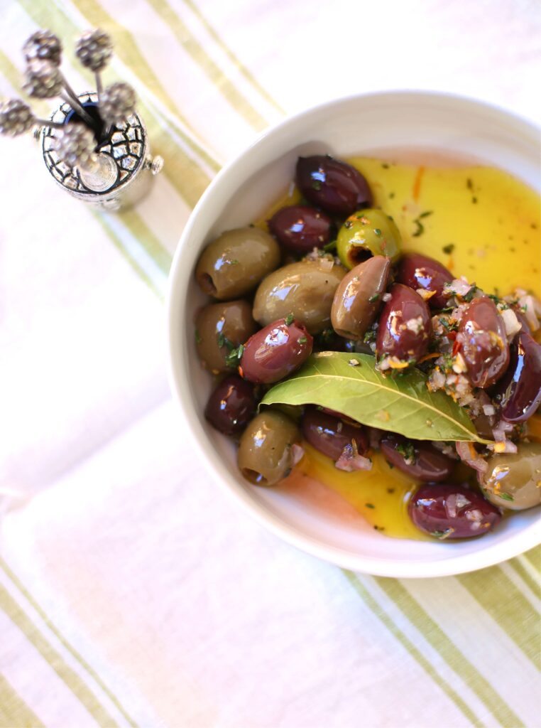 Festive Party Olives in a white bowl with silver toothpicks alongsideby Studio Delicious.com