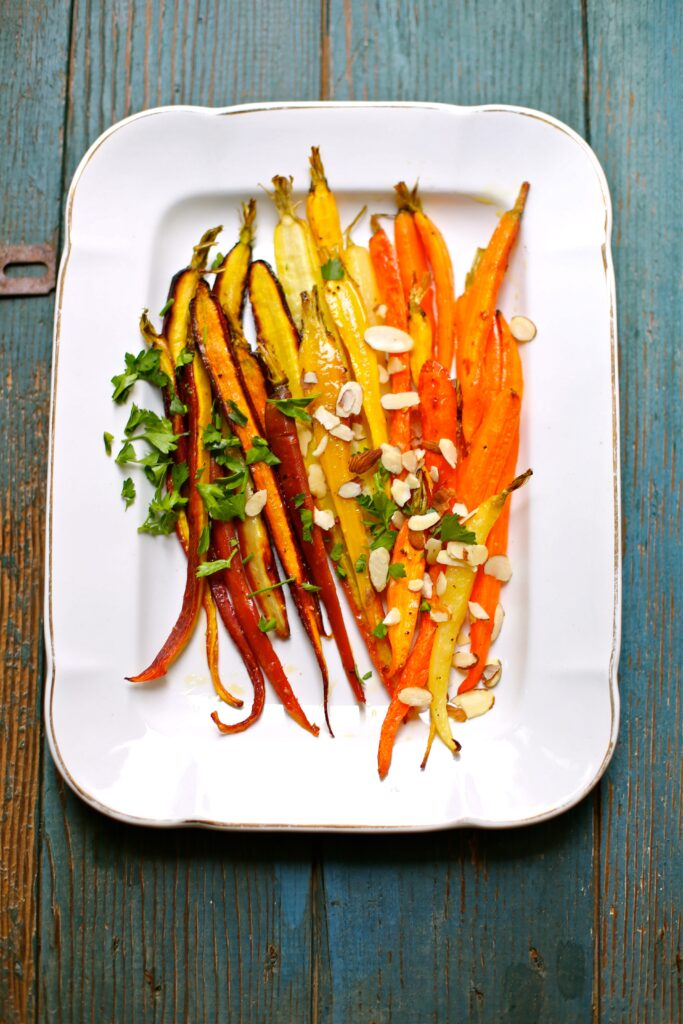 Citrus Roasted Carrots on a white platter with a blue wood background