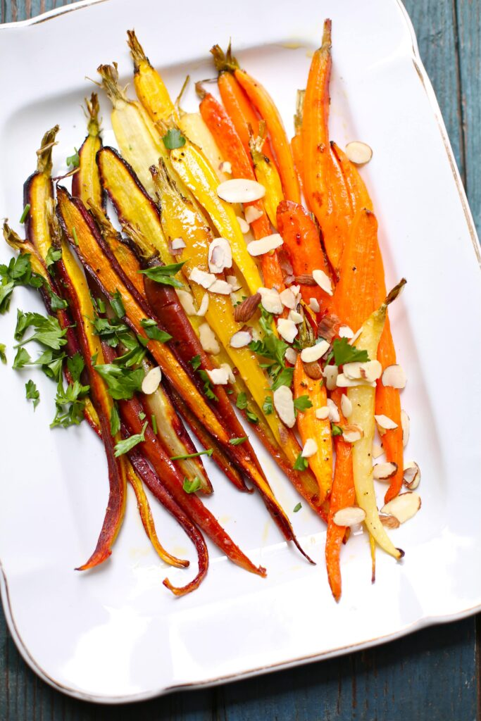 Citrus Roasted Carrots on a white platter with almonds and parsley on top