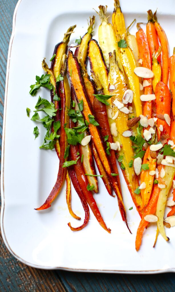 Citrus Roasted Carrots on a white platter with parsley and sliced almonds