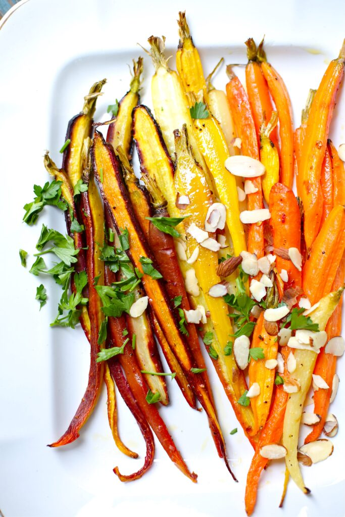 Citrus Roasted Carrots on white platter with parsley and sliced almonds