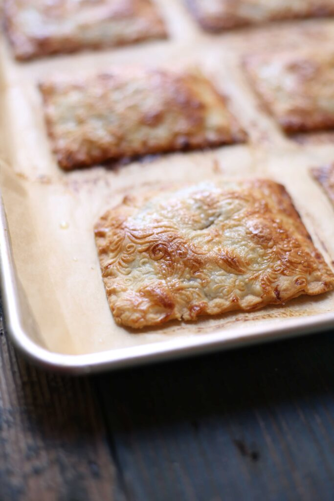 Apple Butter Hand Pies on a baking tray by Studio Delicious