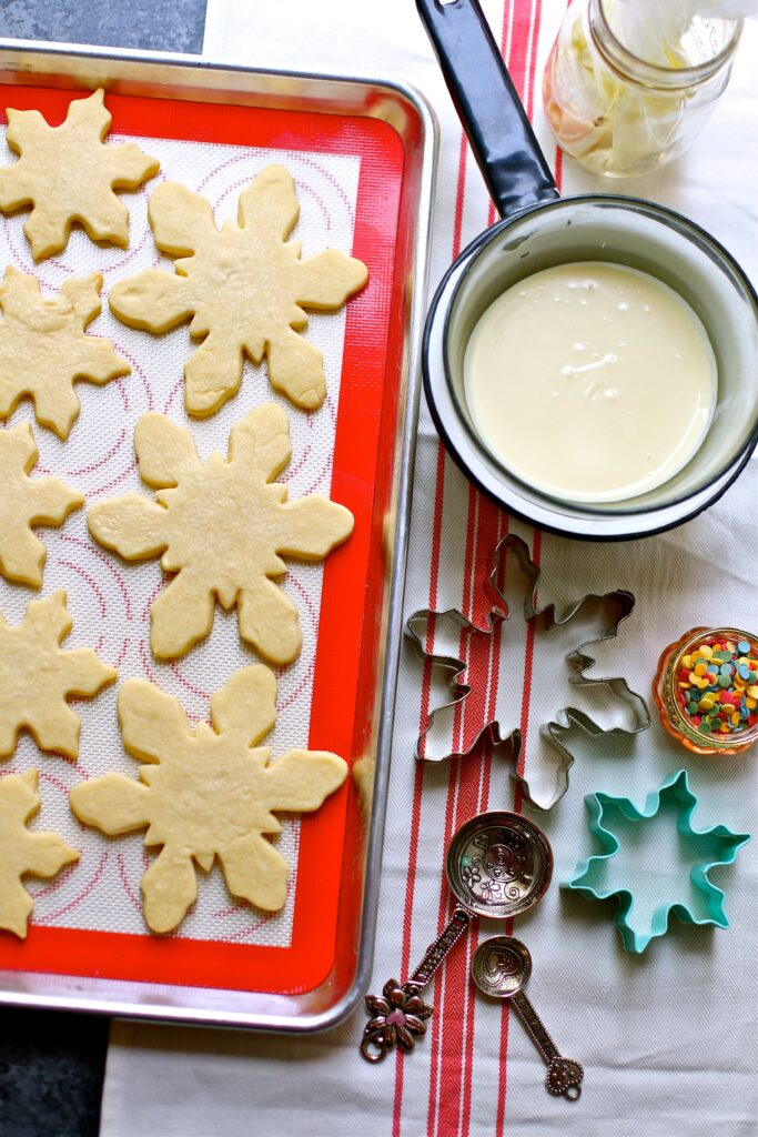 ingredients for White Chocolate Snowflake Cookies, unfrosted with cookie cutters and measuring spoons