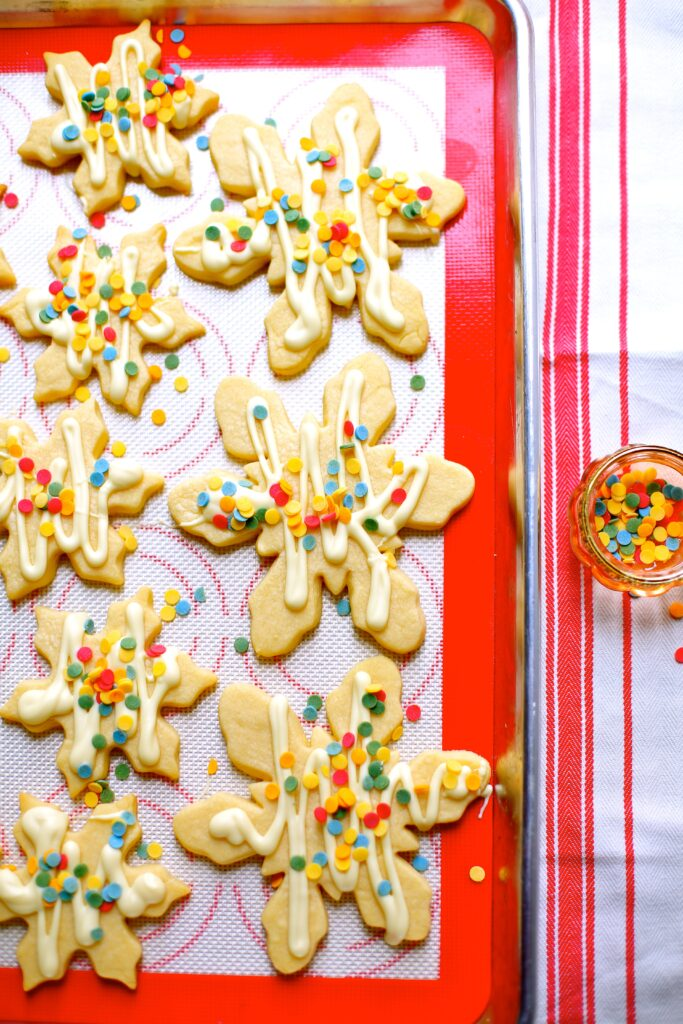 White Chocolate Snowflake Cookies on a tray with red silpat lining