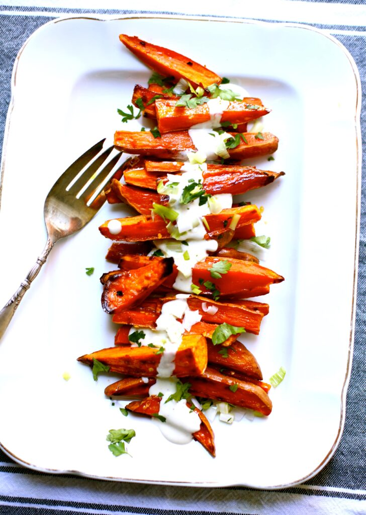 Spicy Roasted Sweet Potatoes with Yogurt Sauce on a white platter with a silver spoon