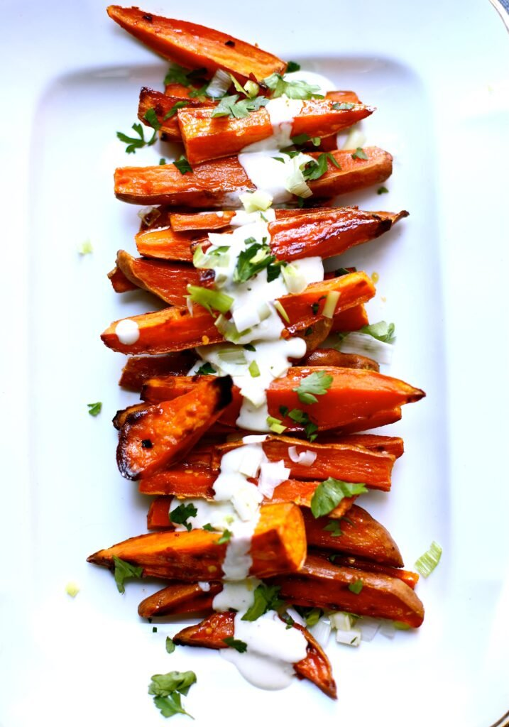 Spicy Roasted Swee Potatoes with Yogurt Sauce on a white tray