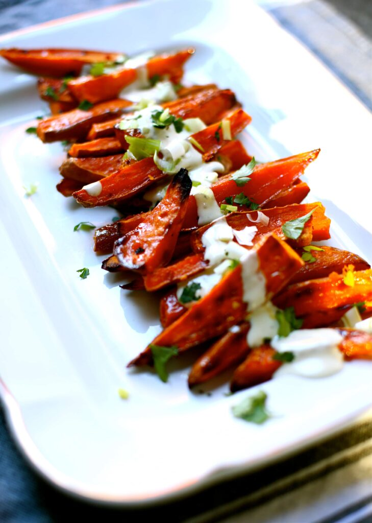 Spicy Roasted Sweet Potatoes with Yogurt Sauce on a white platter
