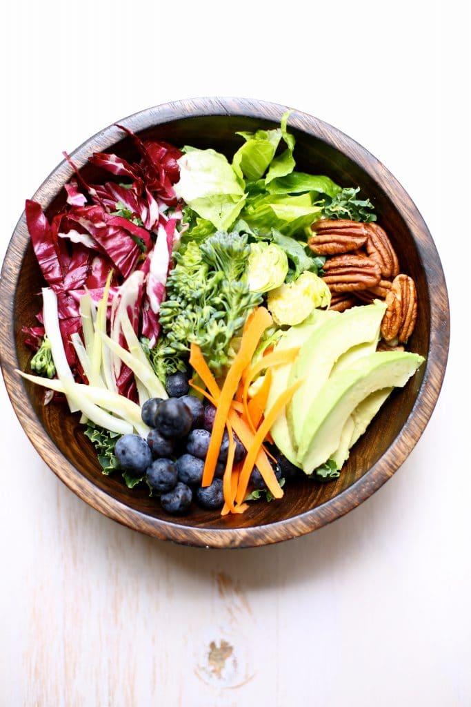 Superfood Salad in a wooden bowl with white background