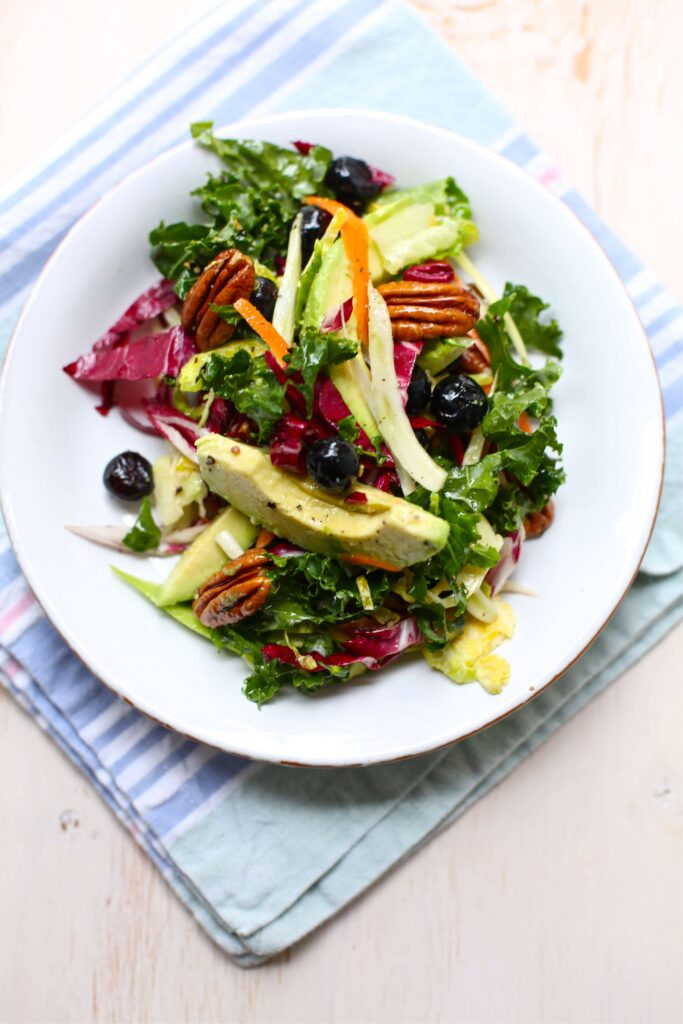 Superfood Salad tossed and placed on a small white plate with blue striped backfground