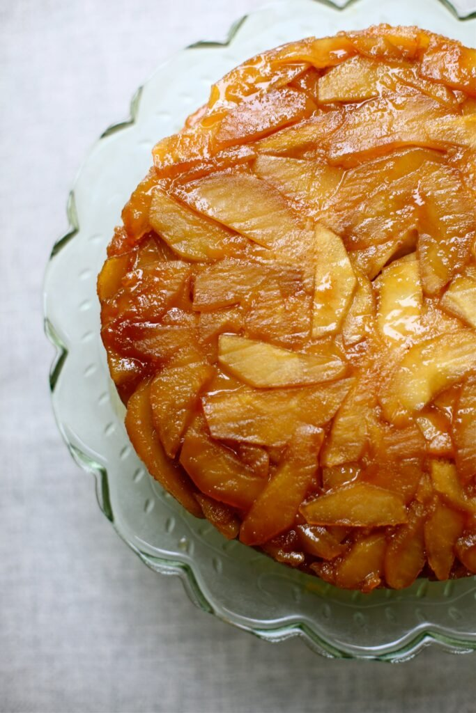 Apple Upside Down Cake on a green glass plate with slate background