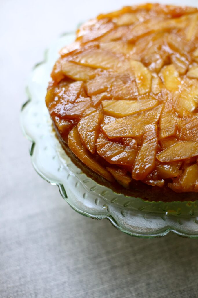 Apple Upside Down Cake on a green glass plate with gray slate background