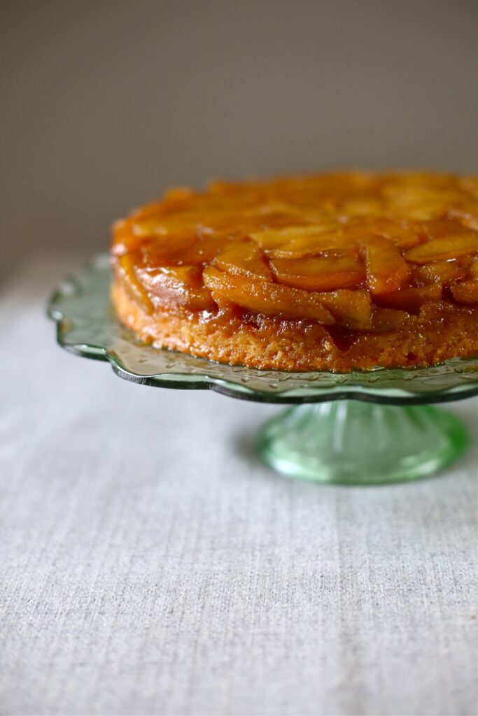 Apple Upside Down Cake on a green glass stand and gray background