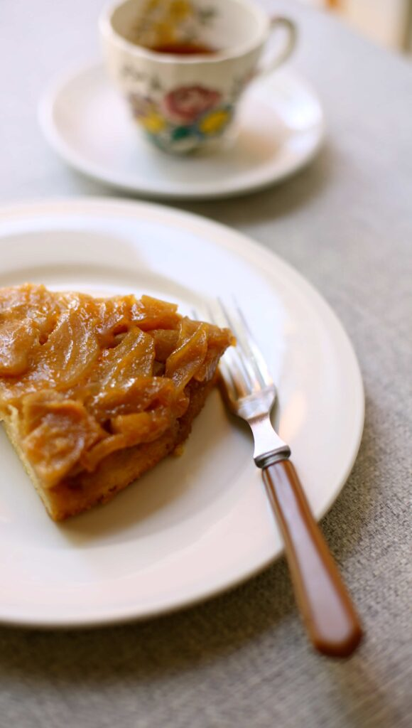 Apple Upside Down Cake slice on a white plate with fork and tea in a cup in the background