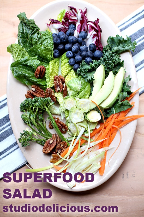 Superfood Salad with text and website address on a white plate with striped background
