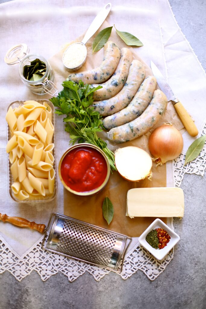 Chicken Sausages, pasta, tomatoe sauce and other ingredients on a table