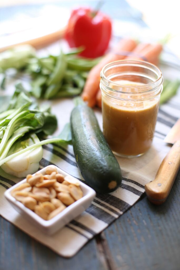 peanut sauce in a jar, zucchini, peas, peanuts, knife and bok choy on a striped napkin
