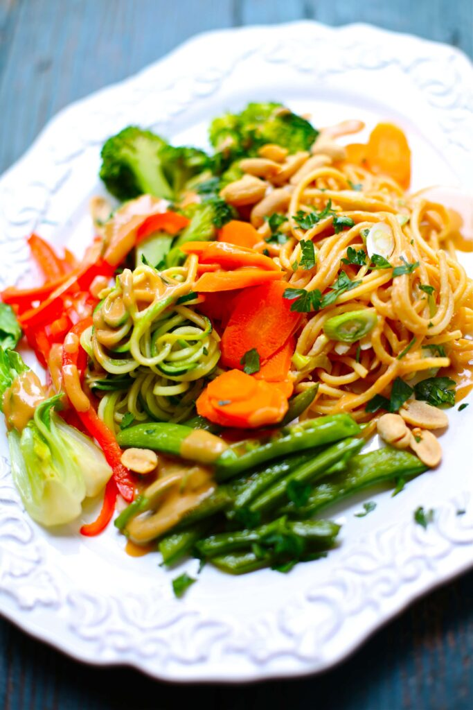 Carrots, sugar snap peas broccoli, red pepper and noodles on a white plate with blue background