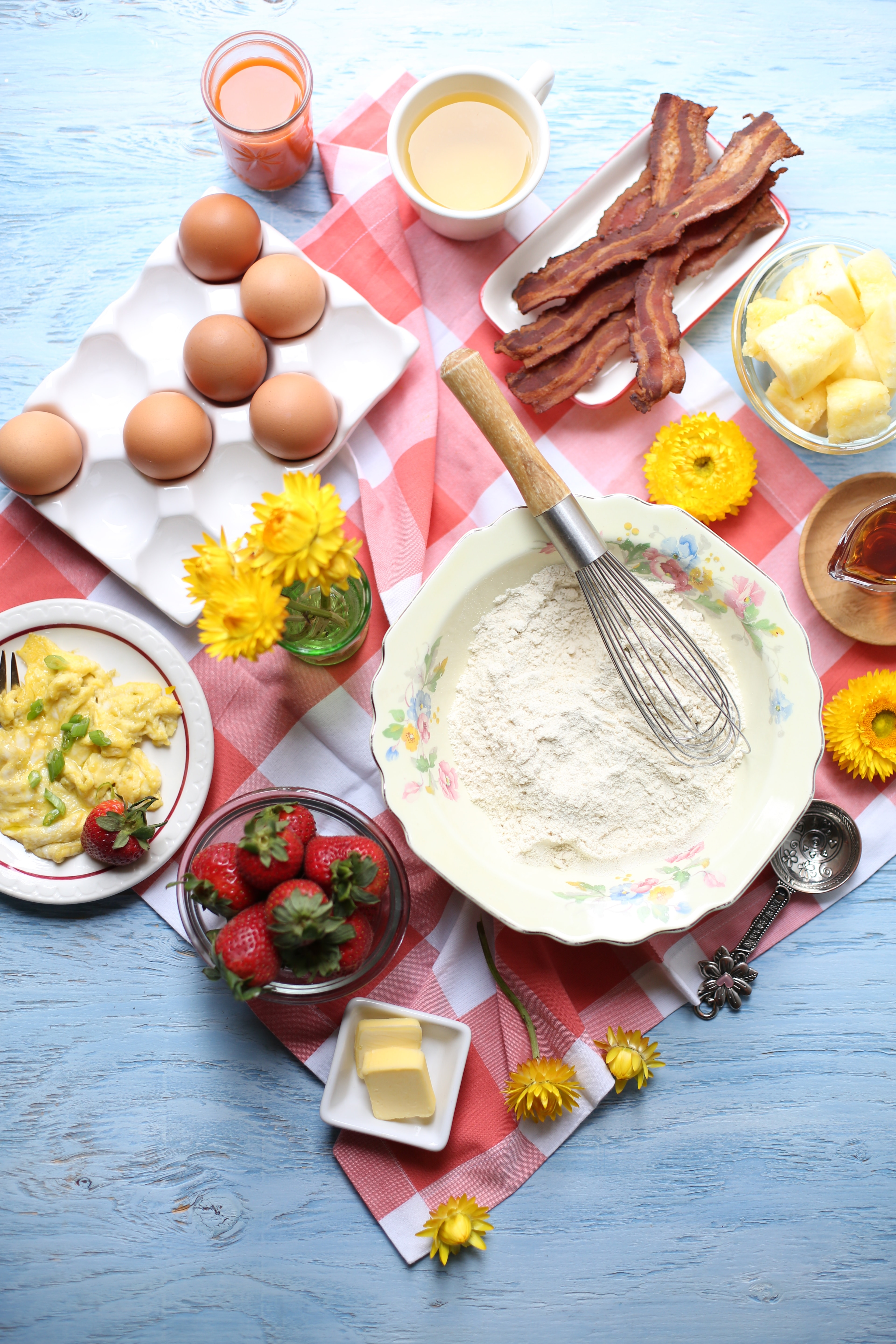 Ingredients on a red checked tablecloth on a blue table. Flour, strawberreis, eggs, bacon, butter and other breakfast items.