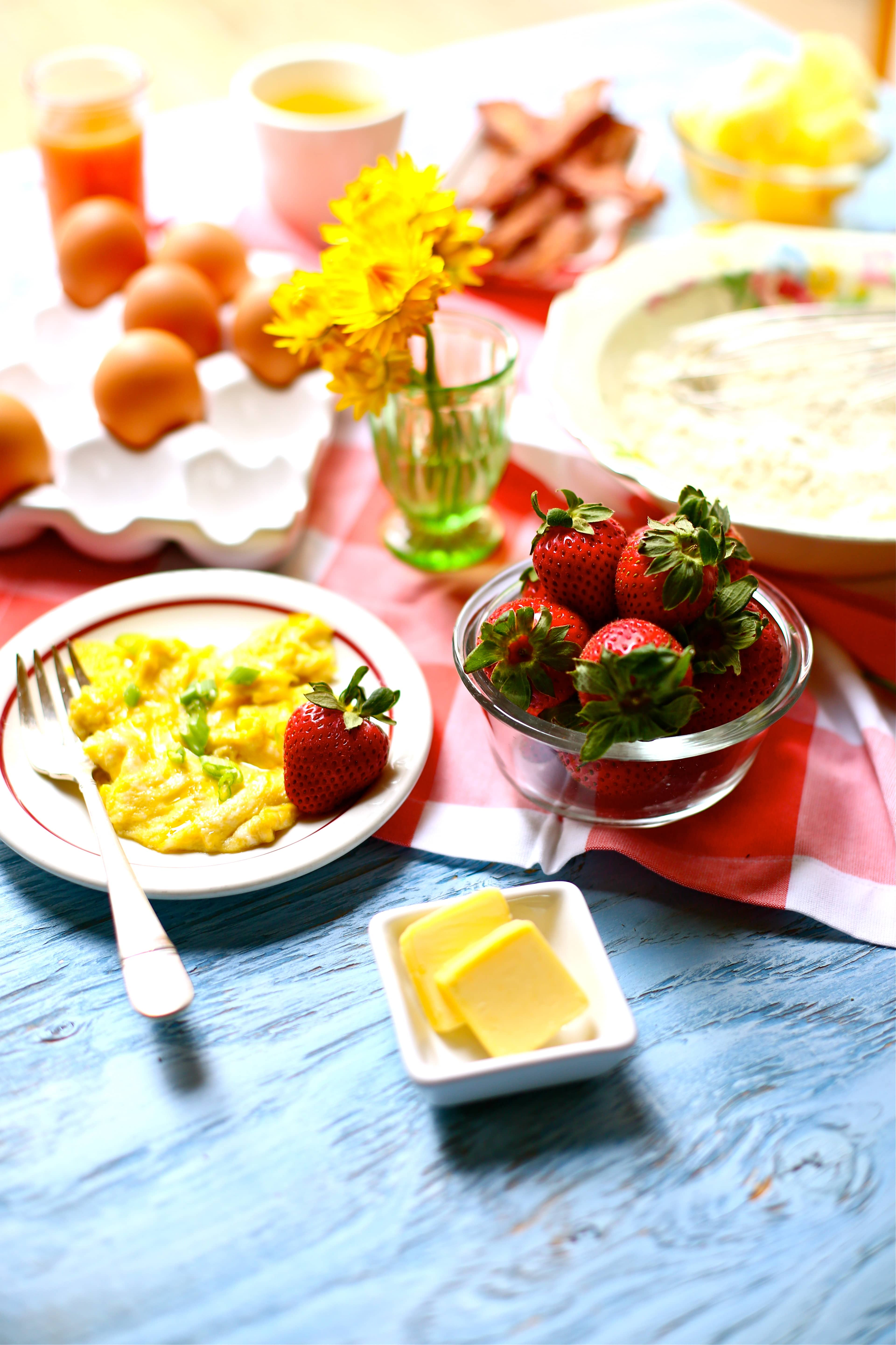 Set up for a Cornmeal Pancakes with Strawberry jam breakfast with scrambled eggs and strawberries