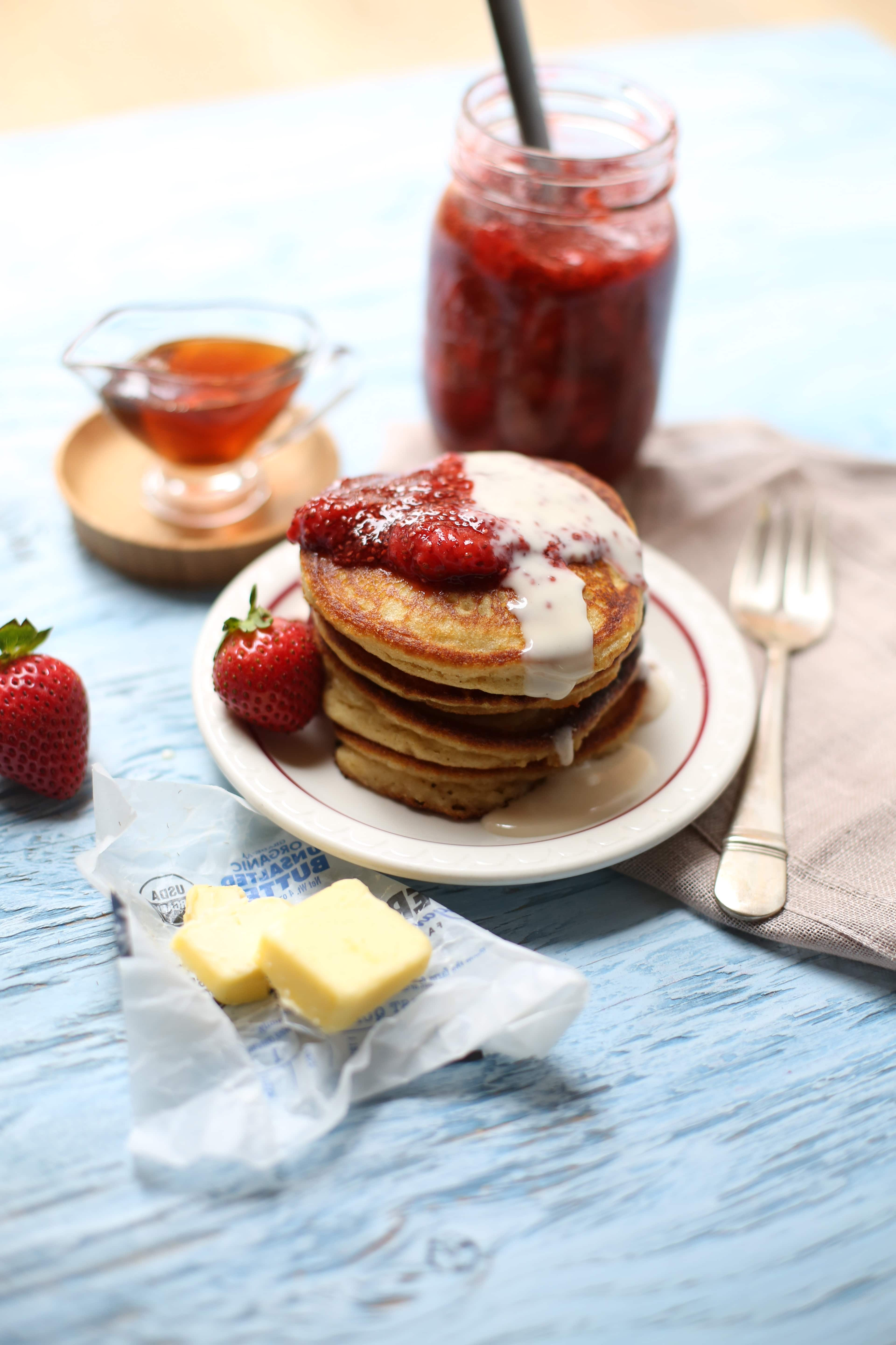 pancakes with strawberries on top and butter alongside with syrup and fork on a table.