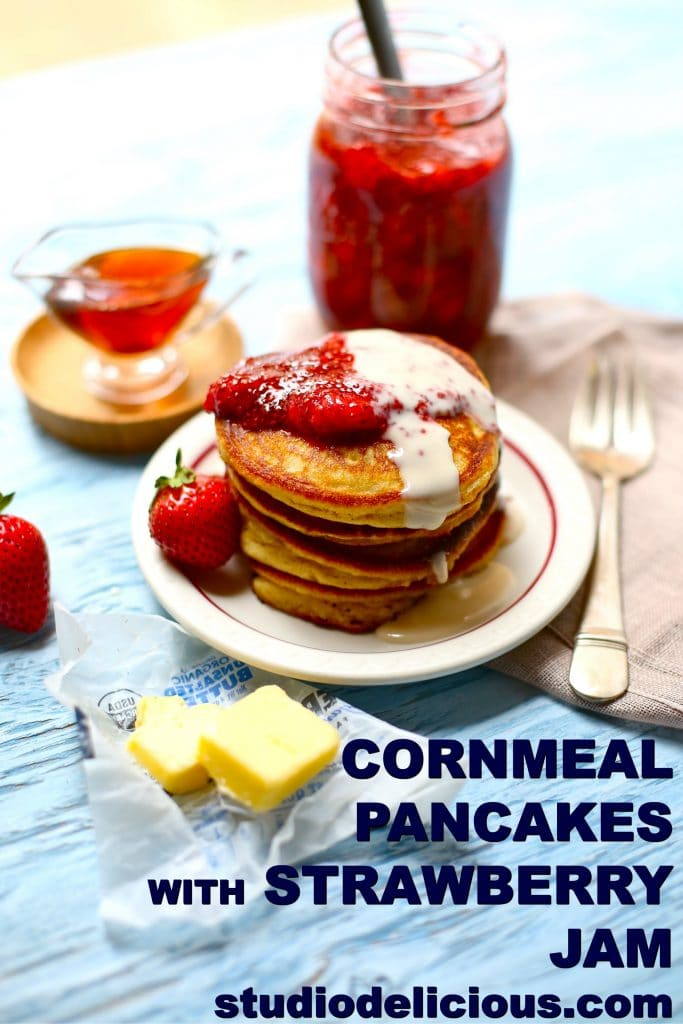 ingredients for cornmeal pancakes with strawberry jam with fork and butter on a blue background