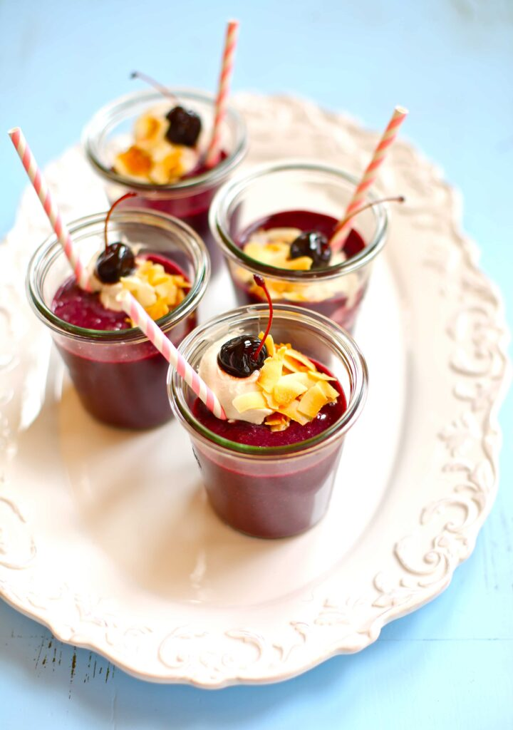 Dark Cherry Smoothies garnished with straws and cherrys and coconut on a white plate with blue background