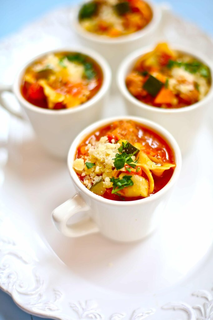 Chicken Tortellini Soup in white cups on white plate