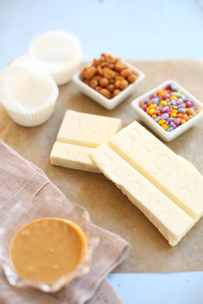 White Valrhona chocolate, colored candies, peanuts, cupcake liners and peanut butter are ingredients for white chocolate peanut butter cups