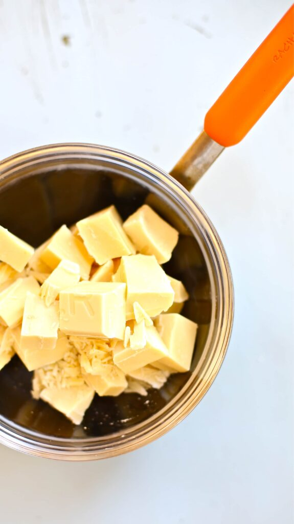 White Chocolate in a medium sized saucepan with orange handle