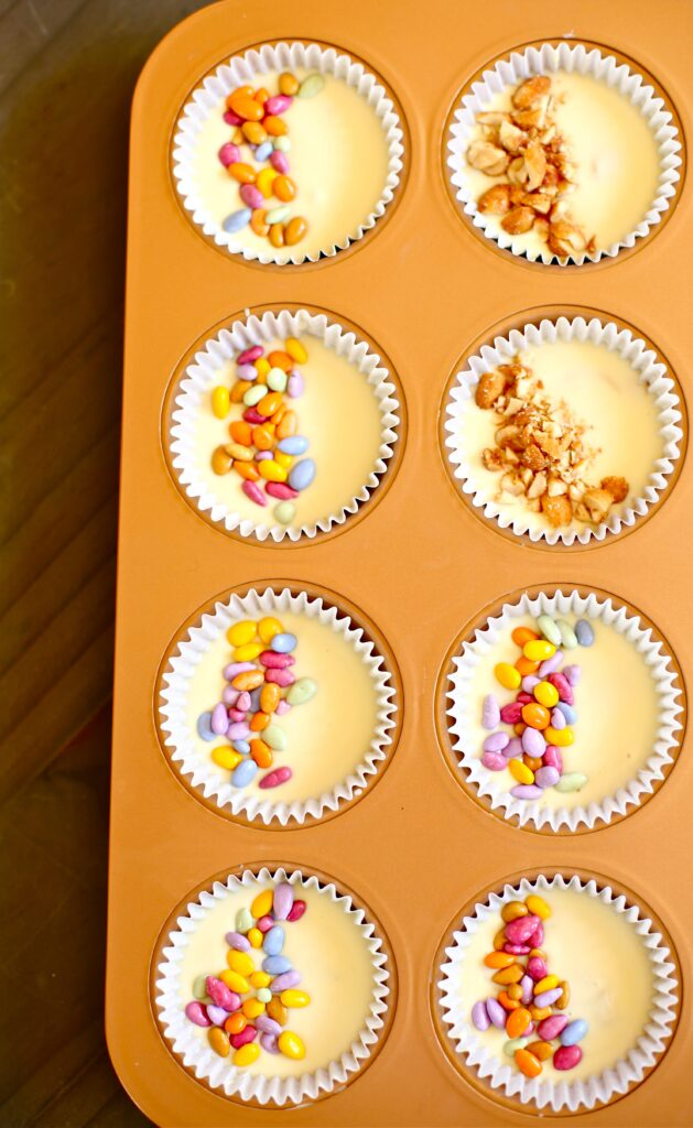 White Chocolate Peant Butter cups with colored candy and peanut garnish in a copper cupcake pan