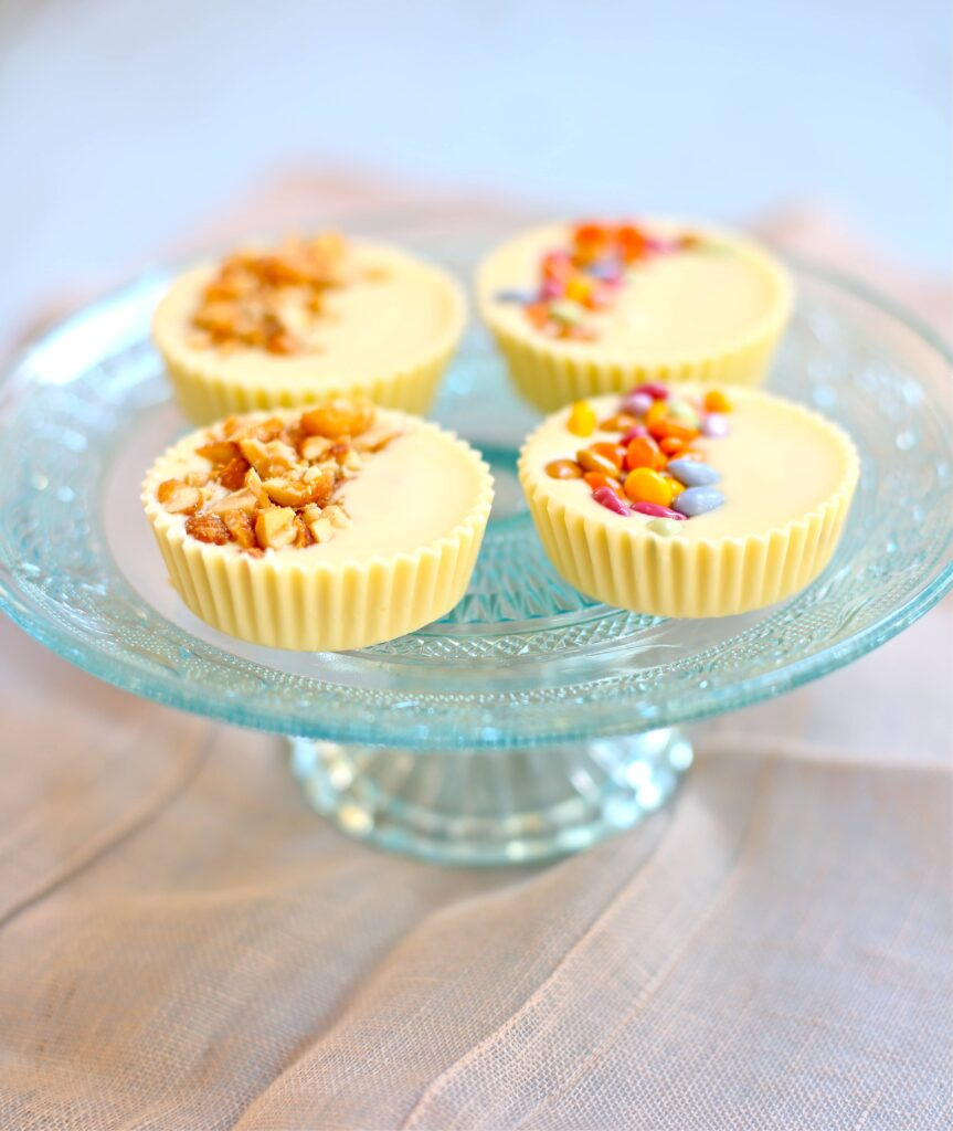 Four white chocolate peanut butter cups with candied topping and peanut topping
