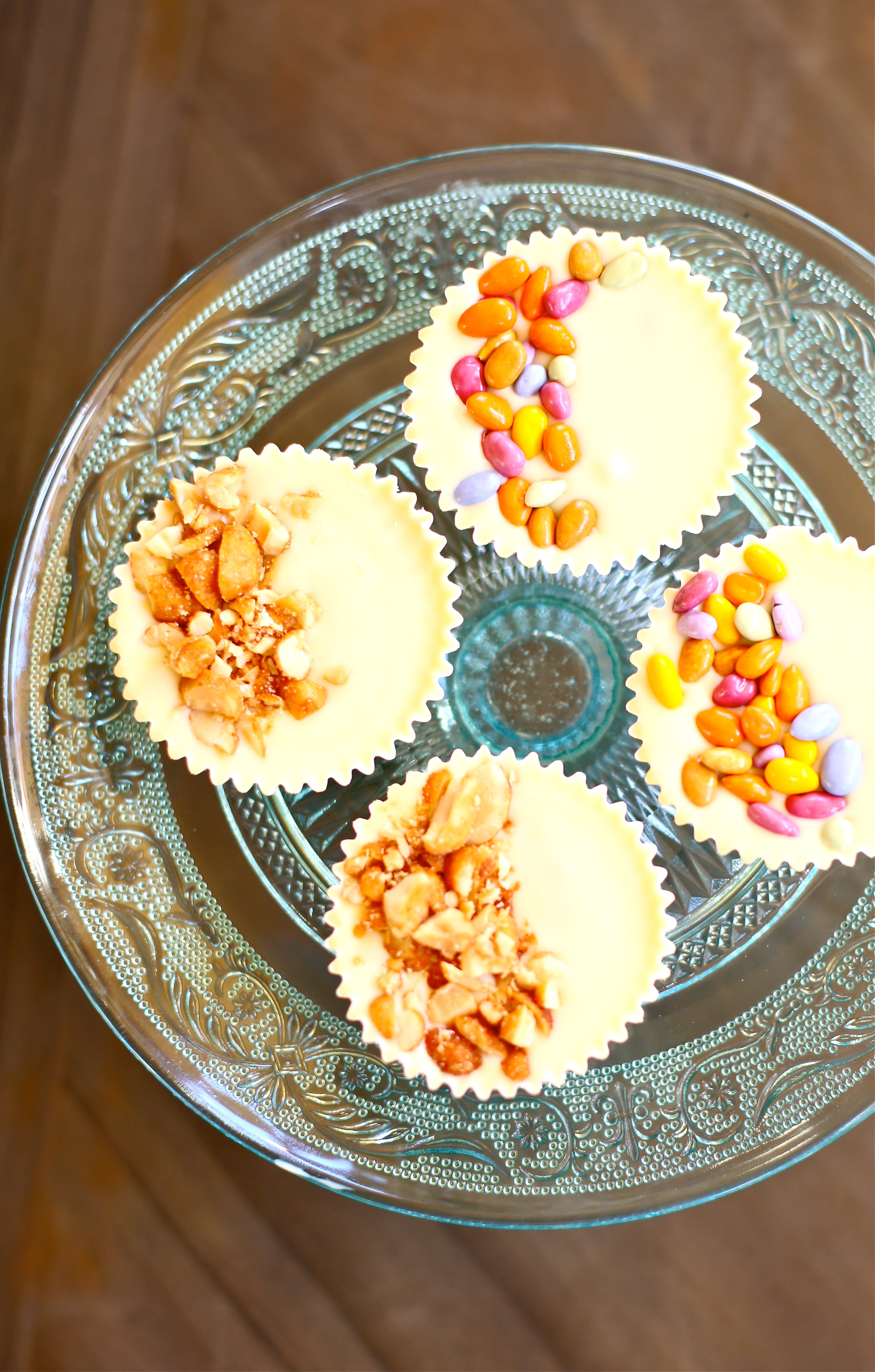 Four white chocolate peanut butter cups with candy and peanut garnishes on a blue plate